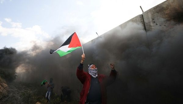 Protester holds a Palestinian flag during clashes with Israeli troops at a protest marking in the West Bank village of Bilin near Ramallah
