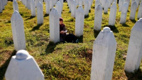 Bosnian Muslim woman prays near a grave before mass funeral in Memorial Center in Potocari near Srebrenica Bosnia and Herzegovina