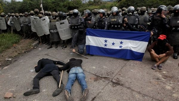 Opposition supporters hold a Honduran flag as others lie on the floor in front of security forces during a protest in Tegucigalpa Honduras Dec. 22 2017