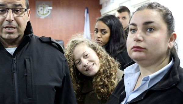 Palestinian teen Ahed Tamimi enters a military courtroom escorted by Israeli Prison Service personnel at Ofer Prison near the West Bank city of Ramallah Jan. 1 2018
