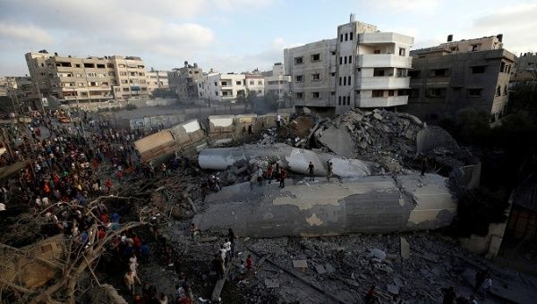 Palestinians gather around a building after it was bombed by an Israeli aircraft in Gaza City